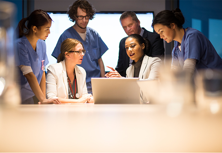 Doctors and nurses talking in front of a lap top