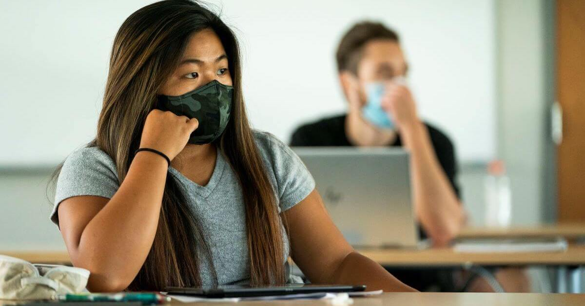 Students wearing masks sit apart in classroom as required by COVID-19 rules.